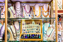 Skärm med olika designer av handgjorda smycken på ställning Royaltyfri Foto