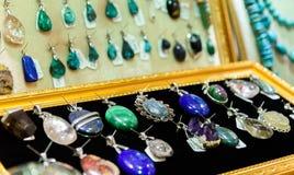Skärm med olika designer av handgjorda smycken på ställning Royaltyfri Fotografi