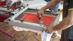 Skärmprintingtillverkning på t-skjortor arkivfilmer