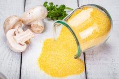 Składniki dla polenty z pieczarkami na drewnianym wieśniaka stole fotografia royalty free