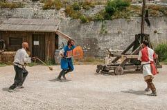 Skådespelare som gör en scenisk byggnadsställning som medeltida kämpar i slotten av Baux-de-Provence Arkivbild
