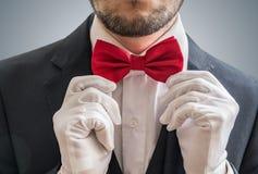 Skådespelaren eller illusionisten i vita handskar tar en röd bowtie Arkivbilder