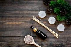 Skóry opieka i relaksuje Kosmetyki i aromatherapy pojęcie Sosnowa zdrój sól, olej na ciemnego drewnianego tła odgórnym widoku i Zdjęcie Royalty Free