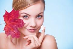 Skóry opieka. Twarz młodej kobiety dziewczyna z czerwonym liściem klonowym. obraz stock