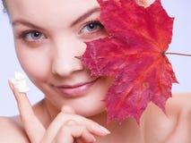 Skóry opieka. Twarz młodej kobiety dziewczyna z czerwonym liściem klonowym. obraz royalty free