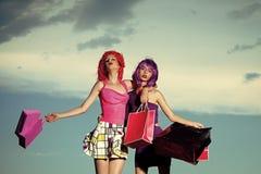 skökor Flickor med konstgjort hår med den färgrika shoppingpåsen Royaltyfri Fotografi