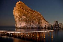 Skönhet av nattdivaen Nattskott av stjärnklart mörkt - blå himmel, vaggar och havet Crimea Ukraina arkivbild