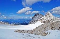 Skönhet av naturen och att förbluffa det alpina landskapet som går i montering, blå himmel, moln, dunsten, dimma, snö täckte berg arkivbild