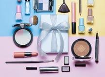 Skönhet, dekorativa skönhetsmedel och gåvaask med pilbågen Makeupborsteuppsättning och färgögonskuggapalett på ljust flerfärgat o royaltyfri bild