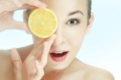 skönhet den unga kvinnan med en halverar av en citron Royaltyfri Bild