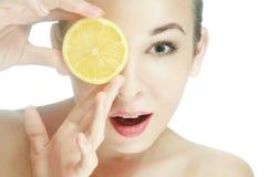 skönhet den unga kvinnan med en halverar av en citron Arkivfoto