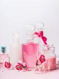 Skönhet och begrepp för hudomsorg på ljus bakgrund, främre sikt Olika kosmetiska produkter i flaskor och krus med rosa blommor Arkivbilder