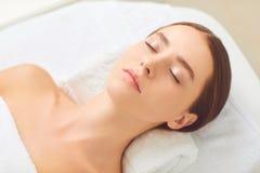 Skönhet och brunnsortbegrepp Brunettflicka som ligger på ett massageskrivbord royaltyfri bild