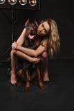 Skönhet och danar Kvinnan med ursnyggt lockigt hår omfamnar dobermanen Mörk bakgrund, flickagrannhuset med en hund Royaltyfri Fotografi
