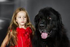 Skönhet och fäflickan med den stora svarta vatten-hunden Royaltyfria Foton
