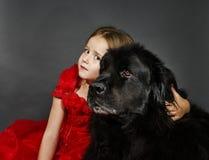 Skönhet och fäflickan med den stora svarta vatten-hunden Royaltyfri Fotografi