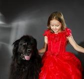 Skönhet och fäflickan med den stora svarta vatten-hunden Arkivfoto