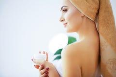 Skönhet och omsorg Kvinnan med ren hud och handduken på huvudet häller royaltyfri bild