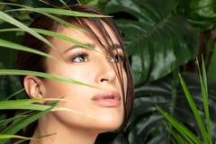 Skönhet och vård- begrepp med en härlig kvinnaframsida som omges av gröna växter arkivfoto