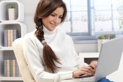 Skönhet som hemma skrivar på bärbar dator Royaltyfri Foto
