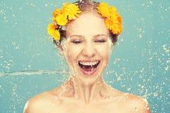 Skönhet som skrattar flickan med färgstänk av vatten och guling, blommar Arkivbild