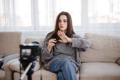 Skönhetblogger för ung kvinna som antecknar den nya videoen royaltyfria bilder