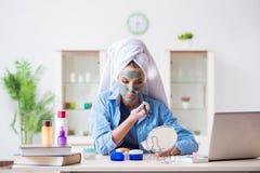 Skönhetbloggeren som applicerar maskeringen och postar till internetbloggen Fotografering för Bildbyråer