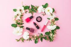 Skönhetbloggerskrivbordet med skönhetsmedel, läppstift, ögonskuggor, spikar polermedel och den rosa ramen av blommor på rosa bakg Arkivbilder