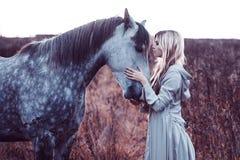 Skönhetblondie med hästen i fältet arkivbild