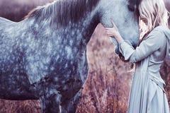Skönhetblondie med hästen i fältet, effekt royaltyfri foto