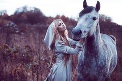 skönhetblondie med hästen i fältet, effekt av toningen arkivbild