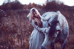 skönhetblondie med hästen i fältet, effekt av toningen arkivfoton