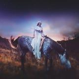 Skönhetblondie på hästrygg, under det sagolikt arkivfoton