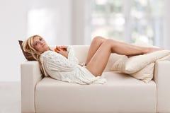 skönhetblondie som lägger sofakvinnan Fotografering för Bildbyråer