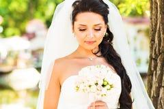 Skönhetbruden i brud- kappa med buketten och snör åt skyler på naturen Härlig modellflicka i en vit bröllopsklänning Arkivfoton