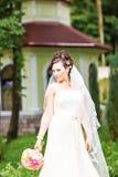 Skönhetbruden i brud- kappa med buketten och snör åt skyler på naturen Härlig modellflicka i en vit bröllopsklänning Royaltyfri Foto
