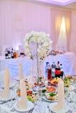 Skönhetbruden i brud- kappa med snör åt skyler kastar bröllopbuketten inomhus Royaltyfri Bild