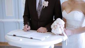 Skönhetbruden och den stiliga brudgummen registrerar förbindelsen stock video