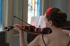 skönhetbrunetten plays fiolen arkivfoton