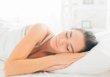 Skönhetbrunettflicka som sover i hennes säng royaltyfri fotografi