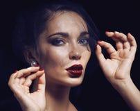 Skönhetbrunettkvinnan under svart skyler med rött Royaltyfri Bild