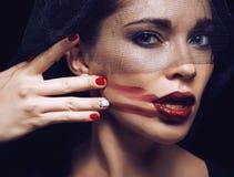 Skönhetbrunettkvinnan under svart skyler med rött Fotografering för Bildbyråer
