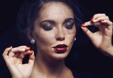 Skönhetbrunettkvinnan under svart skyler med rött Arkivbild