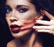Skönhetbrunettkvinnan under svart skyler med rött manikyrslut upp Royaltyfri Foto