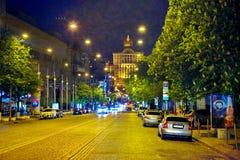 Skönheten av aftonstadsgatan med ljusa ljus av gatalampor med bilar som blomstrar kastanjer på trottoarerna Royaltyfri Foto