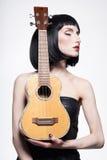 Skönhetflicka i läderklänning med gitarren Arkivfoton