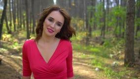 Skönhetflicka i röd klänning med sunt långt hår i skogstående Lycklig kvinna i höst i ultrarapid som ler stock video