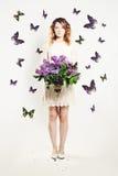 Skönhetflicka med blommor och fjärilen Fotografering för Bildbyråer