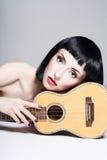Skönhetflicka med den lilla gitarren Royaltyfri Bild