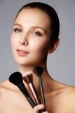Skönhetflicka med makeupborstar Naturligt smink för brunetten Wo arkivbild